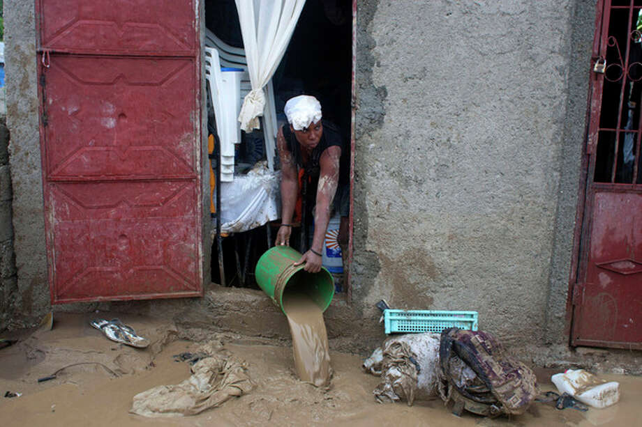 A resident drains mud from a flooded house after heavy rains brought by Hurricane Sandy in Port-au-Prince, Haiti, Thursday, Oct. 25, 2012. Sandy was blamed for the death of an elderly man in Jamaica who was crushed by a boulder. Another man and two women died while trying to cross storm-swollen rivers in southwestern Haiti. (AP Photo/Dieu Nalio Chery) / AP