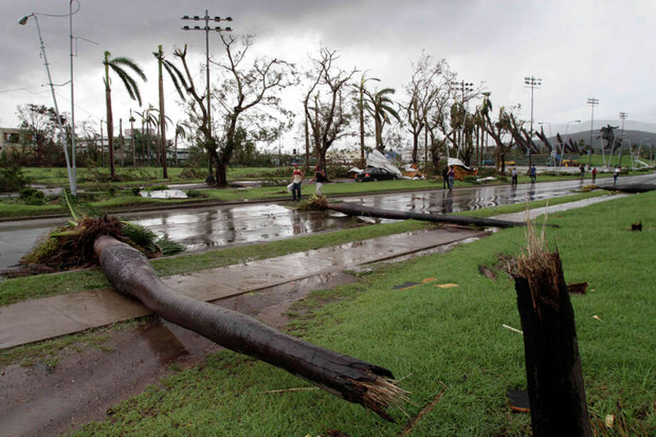 Fallen palm trees lie on a road after the hurricane Sandy in Santiago de Cuba, Cuba, Thursday Oct. 25, 2012. Hurricane Sandy blasted across eastern Cuba on Thursday as a potent Category 2 storm and headed for the Bahamas after causing at least two deaths in the Caribbean. (AP Photo/Franklin Reyes) / AP