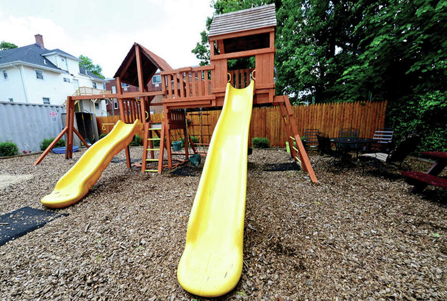 Hour photos / Erik TrautmannAbove, two unidentified children play in the newly renovated playground space for children who are staying at the shelter. Below, some of the new playground equipment. / (C)2013, The Hour Newspapers, all rights reserved