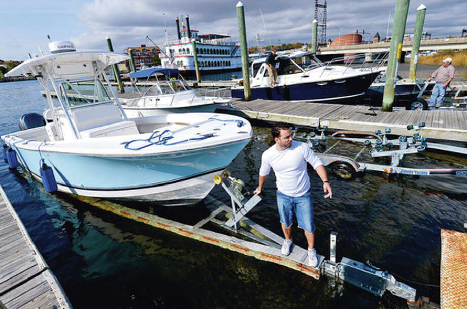 Hour photo / Erik TrautmannRob Padula of Everest Marine takes a client's boat out of the water at Veterans Memorial Park in preparation for the hurricane that is forecast to make landfall in the Northeast. / (C)2012, The Hour Newspapers, all rights reserved