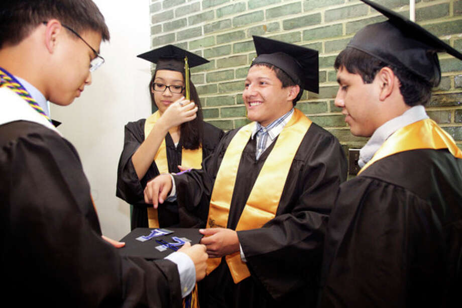 Daniel Acosta helps classmate Cameron Yick with his tassle before AITE's Commencement Exercise at Rippowam Auditorium in Stamford Wednesday evening.Hour Photo / Danielle Calloway