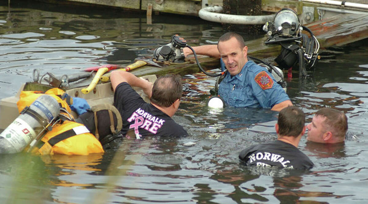 Norwalk Fire and Police Department personnel help in the rescue effort of a couple who plunged into the Norwalk Harbor in their car Saturday.