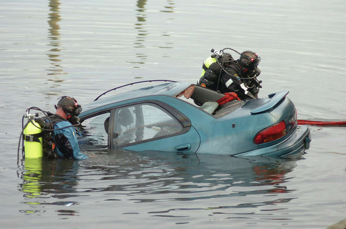 Two divers secure a car that plunged into the water with a driver and passenger inside. After the couple were rescued from the car, divers worked to have the car pulled of the water near the docks at Veterans' Memorial Park on Saturday.