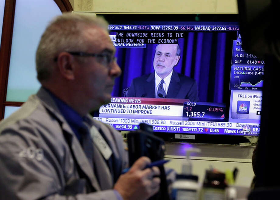 Fed Chairman Ben Bernanke is on a television screen as trader James Dresch works in a booth on the floor of the New York Stock Exchange Wednesday, June 19, 2013. The Federal Reserve offered a hint Wednesday that it's moving closer to slowing its bond-buying program, which is intended to keep long-term interest rates at record lows. (AP Photo/Richard Drew) / AP