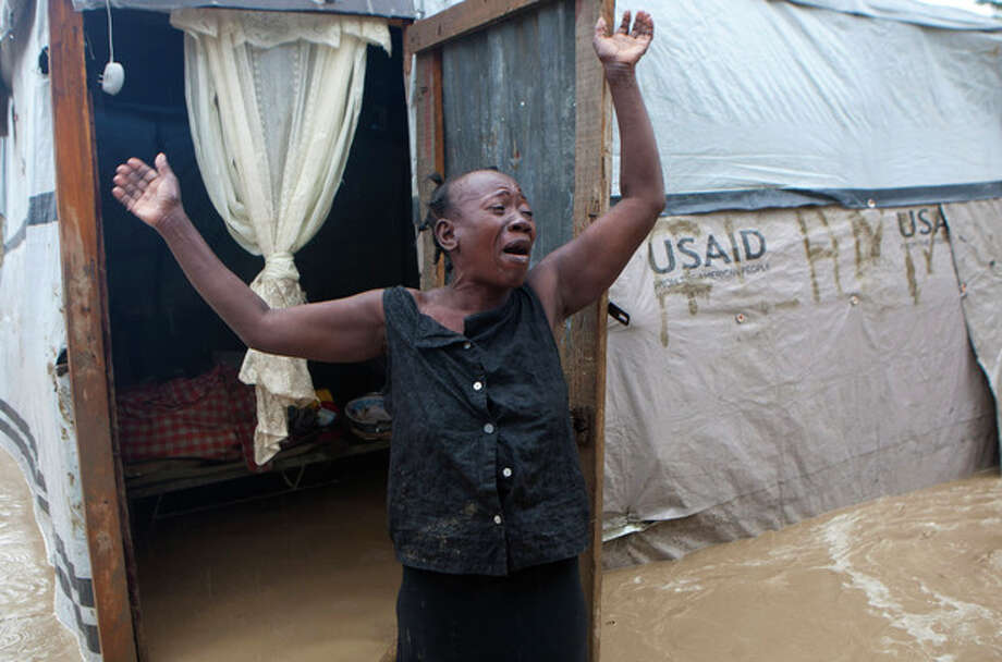 A woman cries out in front of her flooded house caused by heavy rains from Hurricane Sandy in Port-au-Prince, Haiti, Thursday, Oct. 25, 2012. Hurricane Sandy rumbled across mountainous eastern Cuba and headed toward the Bahamas on Thursday as a Category 2 storm, bringing heavy rains and blistering winds. (AP Photo/Dieu Nalio Chery) / AP