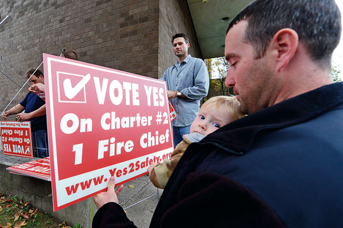 Members of the Stamford Professional Fire Fighters Association including supporter firefighter Greg Beach and son Nathan prepare for a rally across the street from Stamford Fire & Rescue Headquarters Saturday in an effort to urge Stamford voters to vote yes for the passage of Charter Question 2 which would create the position of a single chief for the entire city. Hour photo / Erik Trautmann