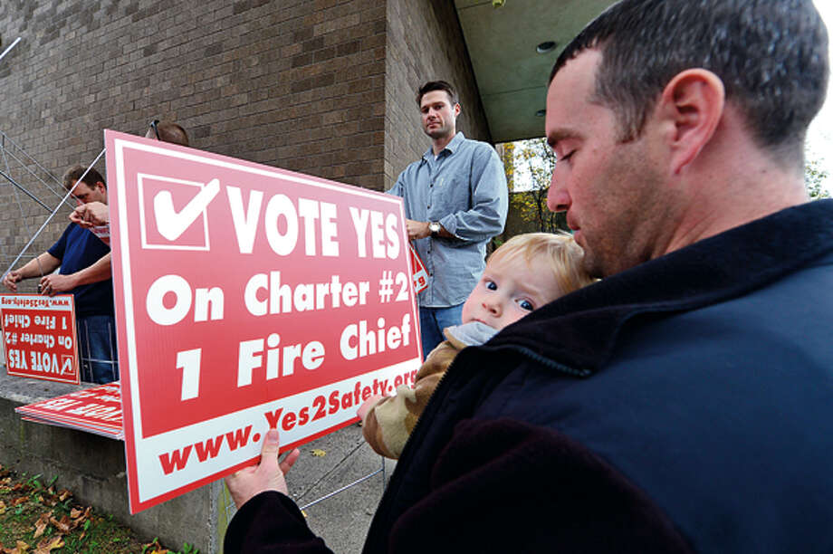 Members of the Stamford Professional Fire Fighters Association including supporter firefighter Greg Beach and son Nathan prepare for a rally across the street from Stamford Fire & Rescue Headquarters Saturday in an effort to urge Stamford voters to vote yes for the passage of Charter Question 2 which would create the position of a single chief for the entire city. Hour photo / Erik Trautmann / (C)2012, The Hour Newspapers, all rights reserved