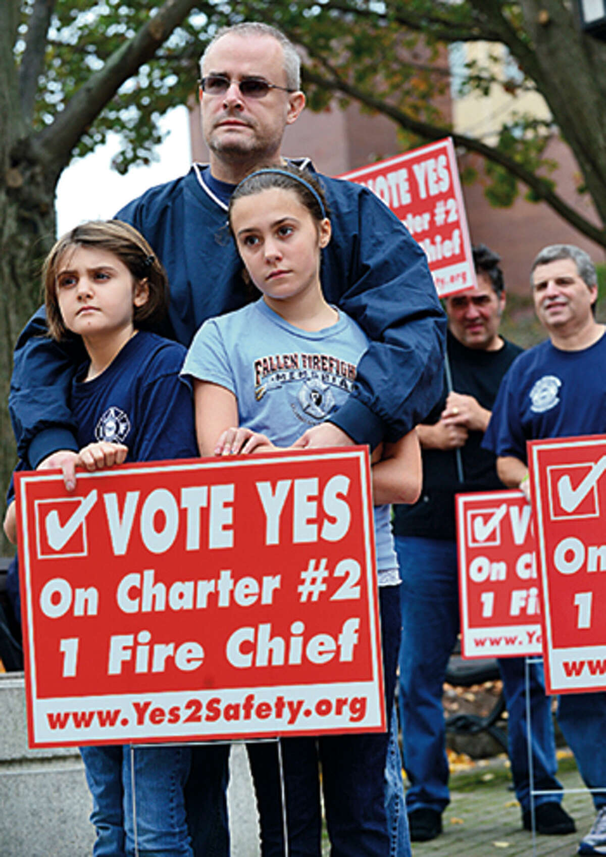Members of the Stamford Professional Fire Fighters Association including Stamford firefghter, Keith Chichester and his daughters, Samantha and Lia, rally across the street from Stamford Fire & Rescue Headquarters Saturday in an effort to urge Stamford voters to vote yes for the passage of Charter Question 2 which would create the position of a single chief for the entire city. Hour photo / Erik Trautmann