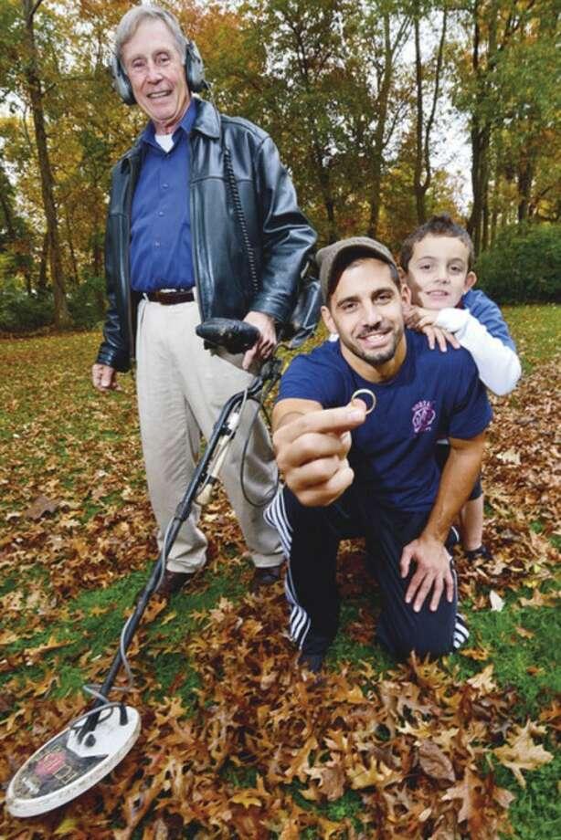 Hour photo / Erik TrautmannMetal detecting enthusiast Dan Godleski, standing, found John Kodonas' wedding ring, which his son Konstantinos had lost four years earlier.