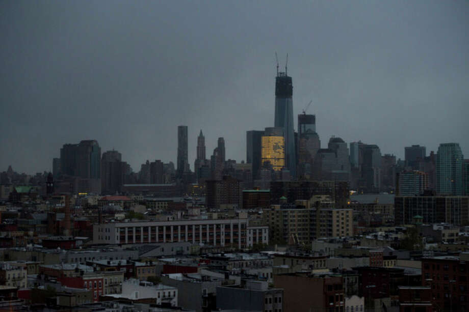 One World Trade Center and large portions of lower Manhattan and Hoboken, N.J., are seen without power from Jersey City, N.J., Tuesday, Oct. 30, 2012, the morning after a powerful storm that started out as Hurricane Sandy made landfall on the East Coast. New York City awakened Tuesday to a flooded subway system, shuttered financial markets and hundreds of thousands of people without power a day after a wall of seawater and high winds slammed into the city, destroying buildings and flooding tunnels. (AP Photo/Charles Sykes) / SYKEC