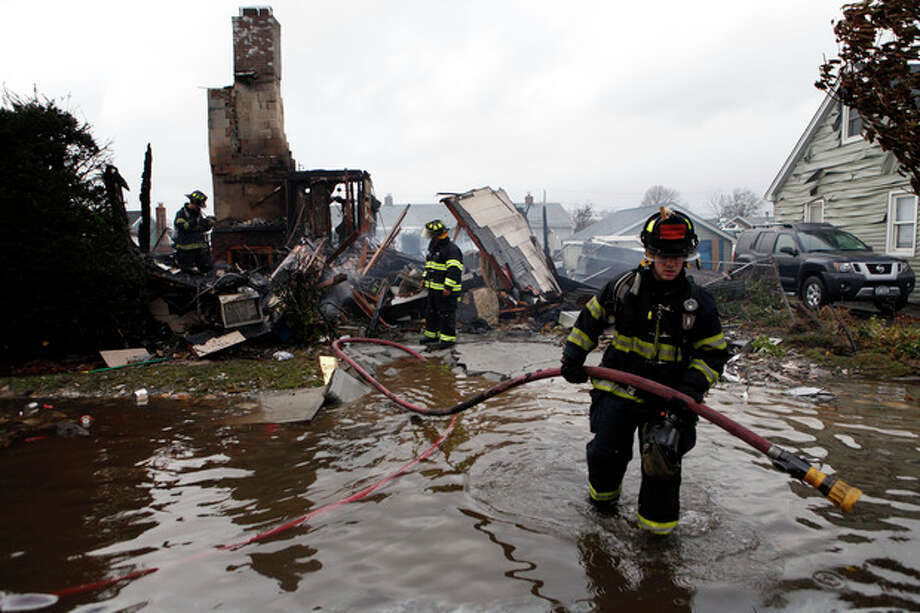 Firefighters work at the scene of a house fire in the aftermath of superstorm Sandy, Tuesday, Oct. 30, 2012, in Lindenhurst, N.Y. According to firefighters at the scene, four homes were destroyed by fire overnight in Lindenhurst, and six in Massapequa. (AP Photo/Jason DeCrow) / FR103966 AP