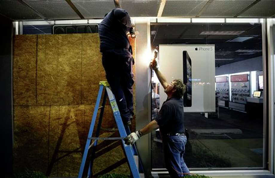 Dwayne Wallace, left, and Brian Rogers board up an AT&T store in Rehoboth Beach, Del. on Saturday, Oct. 27, 2012 as Hurricane Sandy approaches the east coat. (AP Photo/Alex Brandon) / AP