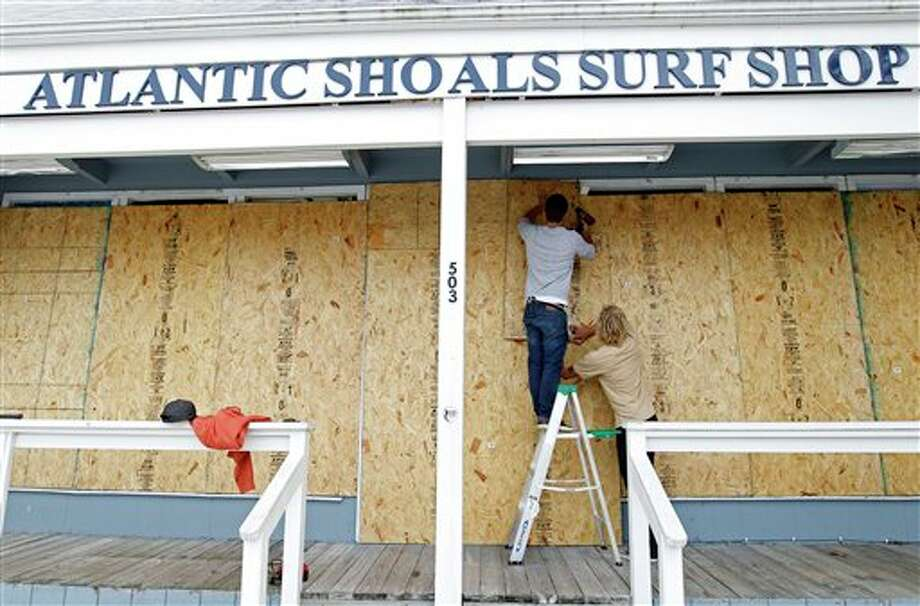 Surf store workers Fletcher Birch, left, and Jay Kleman board up the windows of the store in Ocean City, Md. on Saturday, Oct. 27, 2012 as Hurricane Sandy approaches the Atlantic coast. (AP Photo/Jose Luis Magana) / AP2012