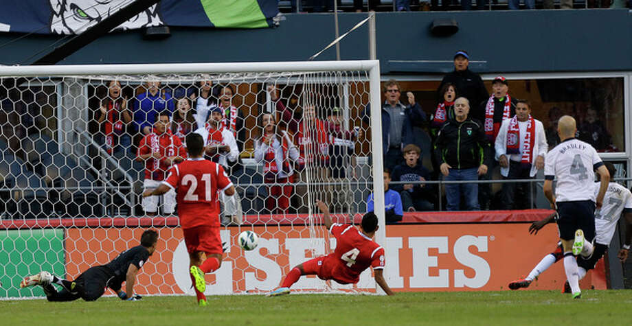 United States' Jozy Altidore (17), far right, scores a goal on Panama goalkeeper Jaime Penedo, left, in the first half of a World Cup qualifier soccer match, Tuesday, June 11, 2013, in Seattle. (AP Photo/Ted S. Warren) / AP