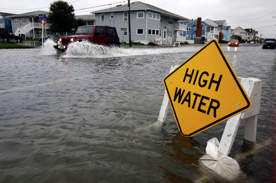 A car goes through the high water as Hurricane Sandy bears down on the East Coast, Sunday, Oct. 28, 2012, in Ocean City, Md. Governors from North Carolina, where steady rains were whipped by gusting winds Saturday night, to Connecticut declared states of emergency. Delaware ordered mandatory evacuations for coastal communities by 8 p.m. Sunday. (AP Photo/Alex Brandon) / AP