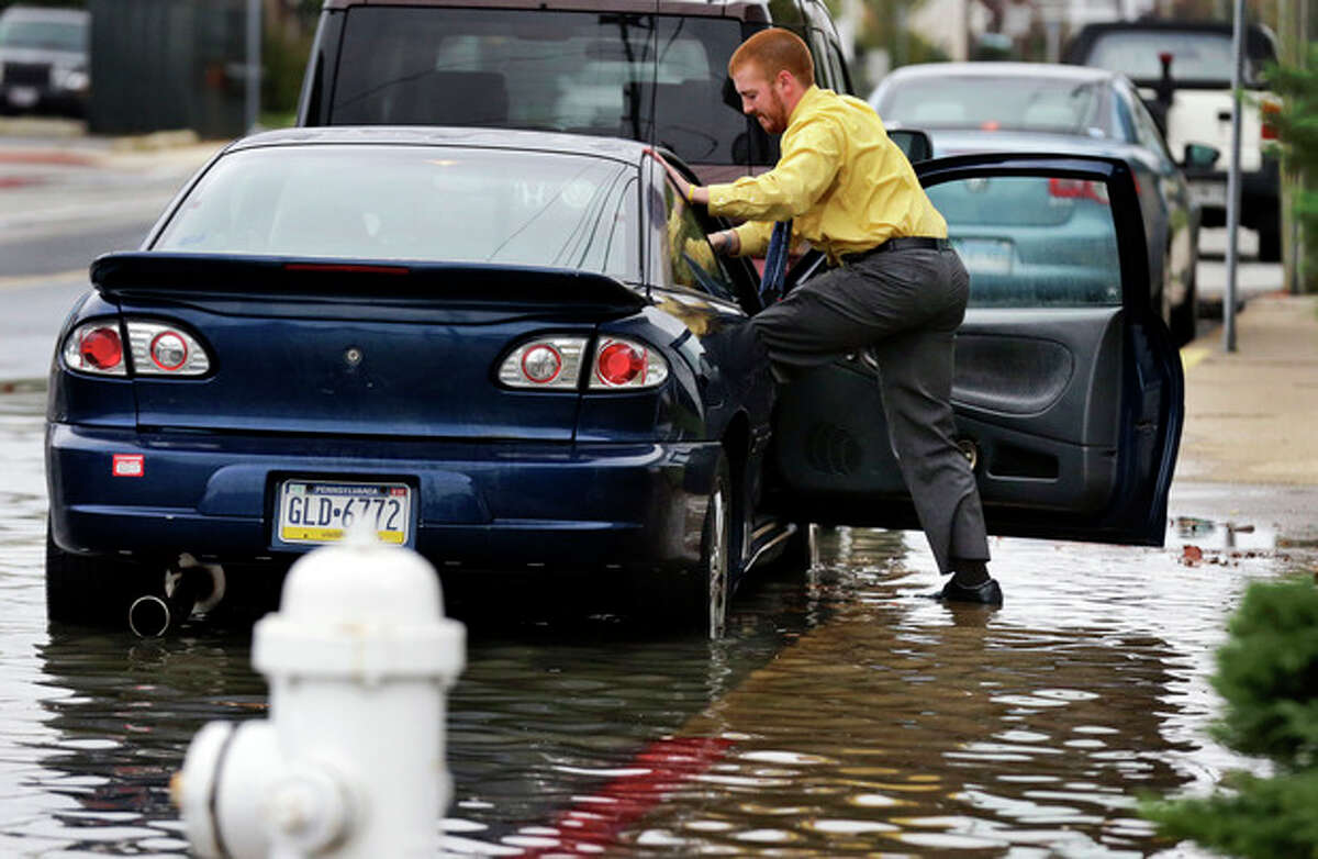 Cody Billotte walks through the high water as he loads his car to go to work as Hurricane Sandy bears down on the East Coast, Sunday, Oct. 28, 2012, in Ocean City, Md. Governors from North Carolina, where steady rains were whipped by gusting winds Saturday night, to Connecticut declared states of emergency. Delaware ordered mandatory evacuations for coastal communities by 8 p.m. Sunday. (AP Photo/Alex Brandon)