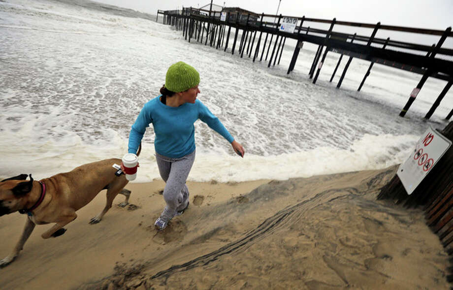 Jenny Lind and her dog Greta run away from a wave that comes up the beach as Hurricane Sandy bears down on the East Coast, Sunday, Oct. 28, 2012, in Ocean City, Md. (AP Photo/Alex Brandon) / AP