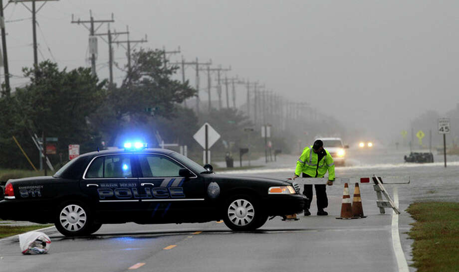 A police officer sets up a road block on South Oregon Inlet Road as water from Hurricane Sandy covers the road in Nags Head, N.C., Sunday, Oct. 28, 2012. (AP Photo/Gerry Broome) / AP