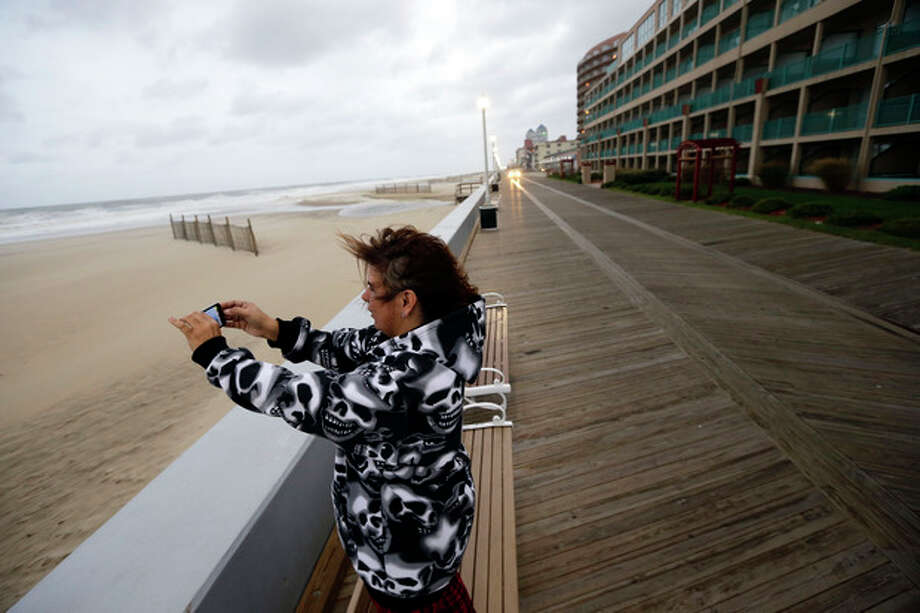 Mary Corrus, from Ocean City, Md., takes a picture of the rough surf as Hurricane Sandy bears down on the East Coast, Sunday, Oct. 28, 2012, in Ocean City, Md. Governors from North Carolina, where steady rains were whipped by gusting winds Saturday night, to Connecticut declared states of emergency. Delaware ordered mandatory evacuations for coastal communities by 8 p.m. Sunday. (AP Photo/Alex Brandon) / AP
