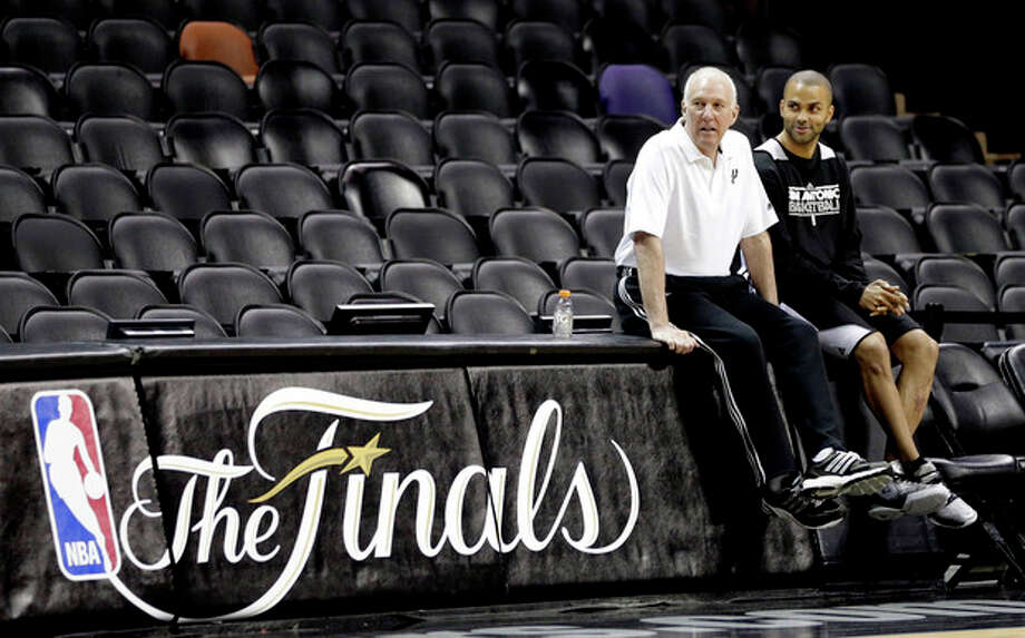 San Antonio Spurs' Tony Parker, right, sits with coach Gregg Popovich during NBA basketball practice Wednesday, June 12, 2013, in San Antonio. The Spurs lead the Miami Heat 2-1 in the best-of-seven games series. Game 4 of the NBA finals series is scheduled for Thursday. (AP Photo/David J. Phillip) / AP