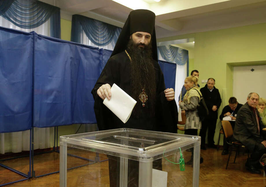 An Orthodox priest casts his ballot paper at a polling station in Kiev, Ukraine, Sunday, Oct. 28, 2012. Voters in Ukraine are choosing a new parliament Sunday. (AP Photo/Efrem Lukatsky) / AP