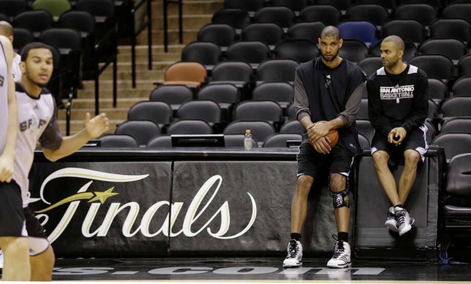 San Antonio Spurs' Tim Duncan, left, and guard Tony Parker, right, of France, talk during a practice, Wednesday, June 12, 2013, in San Antonio. San Antonio will face the Miami Heat in game 4 of the NBA Finals basketball game Thursday. San Antonio leads the best-of-seven series 2-1. (AP Photo/Eric Gay) / AP