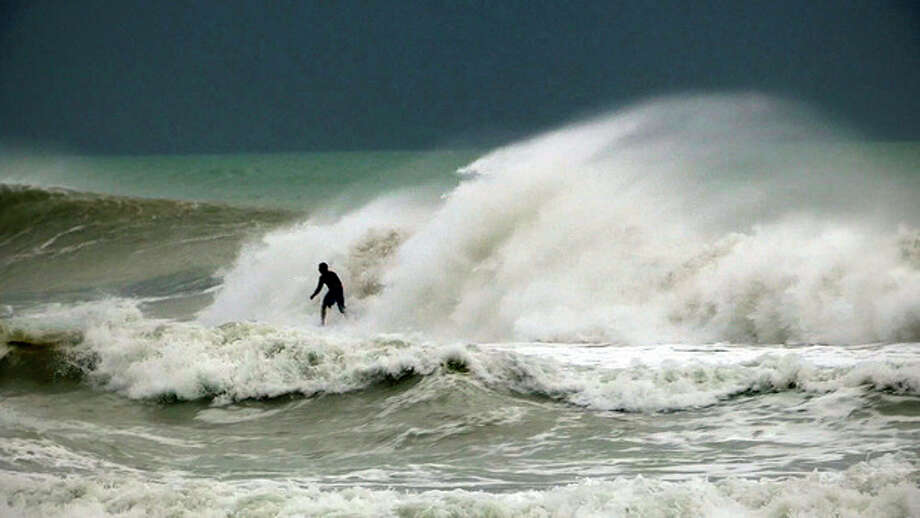 A surfer rides some of the rare waves driven by Hurricane Sandy at South Beach in Miami Friday, Oct. 26, 2012. Hurricane Sandy rolled out of the Bahamas on Friday after causing 40 deaths across the Caribbean, churning toward the U.S. East Coast, where it threatens to join forces with winter weather fronts to create a devastating super storm. (AP Photo/The Miami Herald, Chuck Fadely) MAGS OUT / The Miami Herald