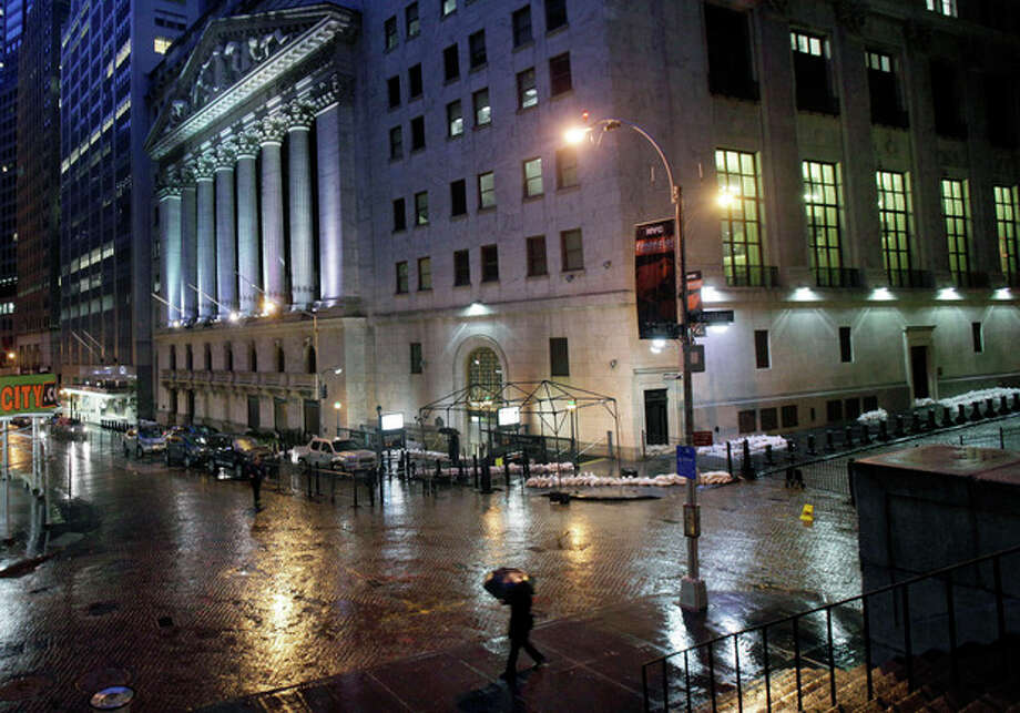 Sand bags protect the front of the New York Stock Exchange, Monday, Oct. 29, 2012. Hurricane Sandy continued on its path Monday, forcing the shutdown of mass transit, schools and financial markets, sending coastal residents fleeing, and threatening a dangerous mix of high winds and soaking rain. There had been plans to allow electronic trading to go forward on the New York Stock Exchange but with a storm surge expected to cover parts of lower Manhattan in water, officials decided late Sunday that it was too risky to ask any personnel to staff the exchanges. (AP Photo/Richard Drew) / AP
