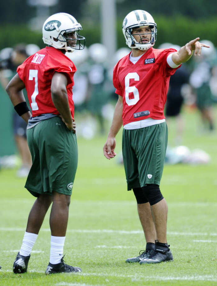 New York Jets quarterbacks Mark Sanchez (6) and Geno Smith (7) talk during NFL football minicamp Tuesday, June 11, 2013, in Florham Park, N.J. (AP Photo/Bill Kostroun)