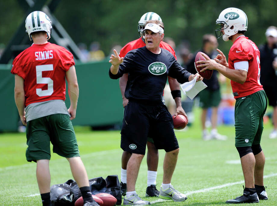 New York Jets quarterbacks coach David Lee, center, talks with quarterbacks Matt Simms (5) and Mark Sanchez, right, during NFL football minicamp Tuesday, June 11, 2013, in Florham Park, N.J. (AP Photo/Bill Kostroun) / FR51951 AP
