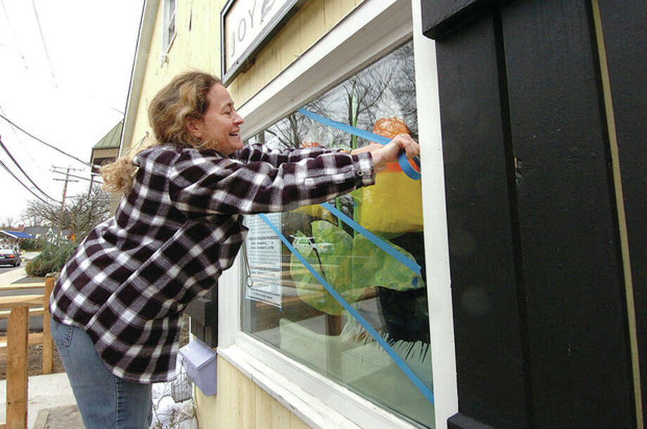 Hour Photo Alex von Kleydorff; Owner Joyce Bottone tapes the windows on her shop Joy 2 Crafts on Riverside Ave Westport / 2012 The Hour Newspapers