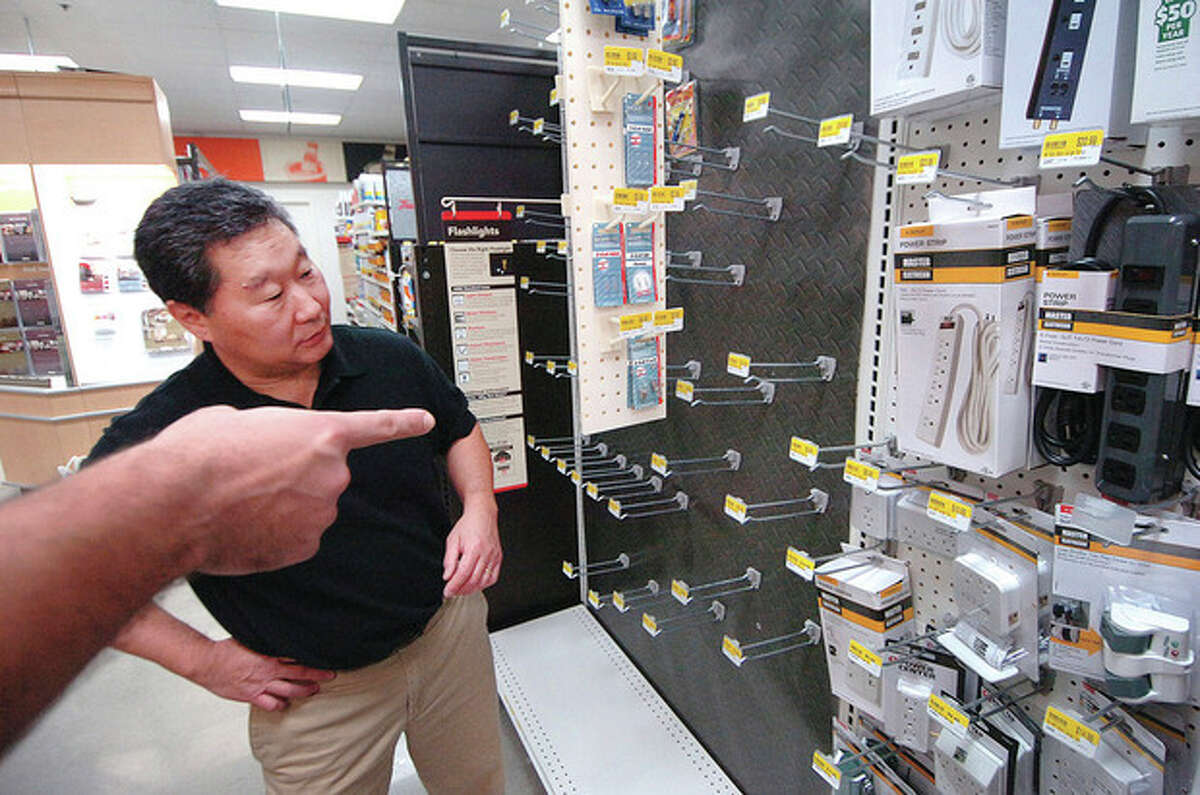 Hour Photo Alex von Kleydorff; Tom Sato owner of Wilton Hardware helps a customer to find whats left of the batteries he has sold out of
