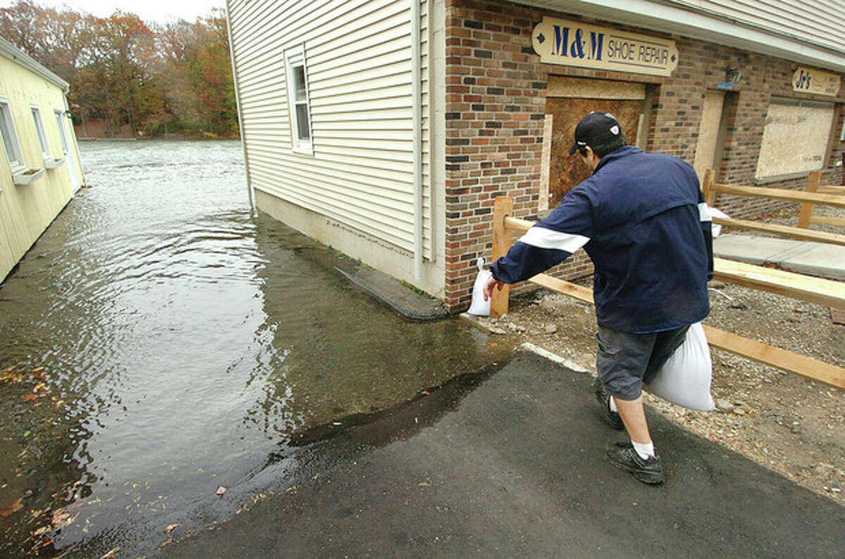Hour photo / Alex von Kleydorff Jeff Arciola, owner of Jr.'s Hot Dogs and Deli, sets a few more sand bags around his store as the Saugatuck River rises along Riverside Avenue in Westport on Monday morning.