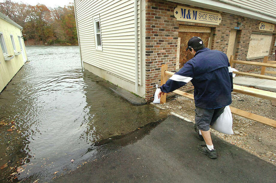 Hour photo / Alex von KleydorffJeff Arciola, owner of Jr.'s Hot Dogs and Deli, sets a few more sand bags around his store as the Saugatuck River rises along Riverside Avenue in Westport on Monday morning. / 2012 The Hour Newspapers