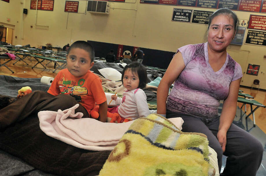 Maria DeJesus and her children, Diego 4 and Casey 2, are set up for the overnight stay at Brien McMahon high school Monday. The Red Cross has the gym available as a shelter from hurrican Sandy. hour photo/Matthew Vinci / (C)2011 {your name}, all rights reserved