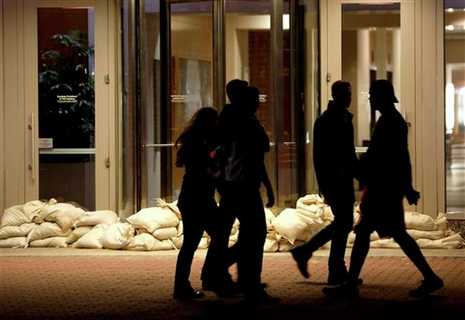 Sandbags line the entrance of a building as people walk by near the Hudson River water front, Sunday, Oct. 28, 2012, in Hoboken, N.J. Tens of thousands of people were ordered to evacuate coastal areas Sunday as big cities and small towns across the U.S. Northeast braced for the onslaught of a superstorm threatening some 60 million people along the most heavily populated corridor in the nation. (AP Photo/Julio Cortez) / AP