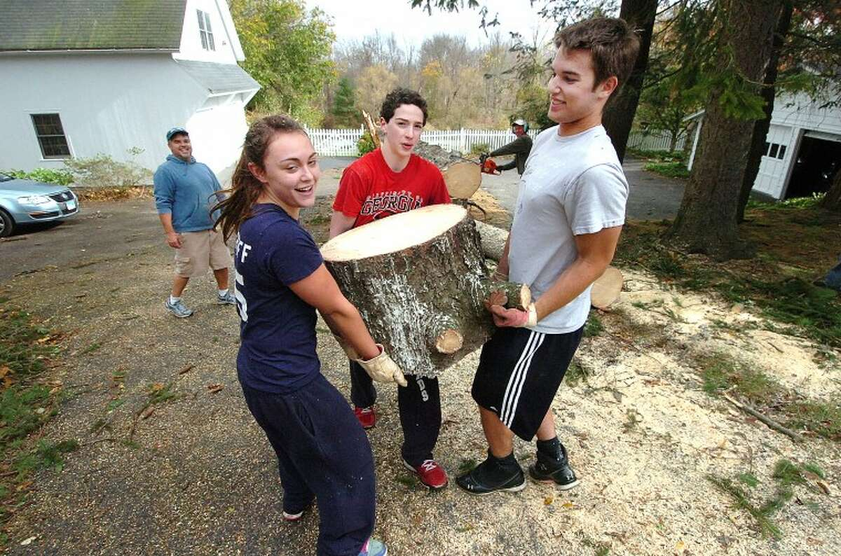 Hour Photo Alex von Kleydorff; l-r Cameron Langnoff Derek Nussbaum and Ben Rappaport lift and haul away for family freinds a cut section form one of two giant white pines that came down along Chestnut Hill rd in Wilton.