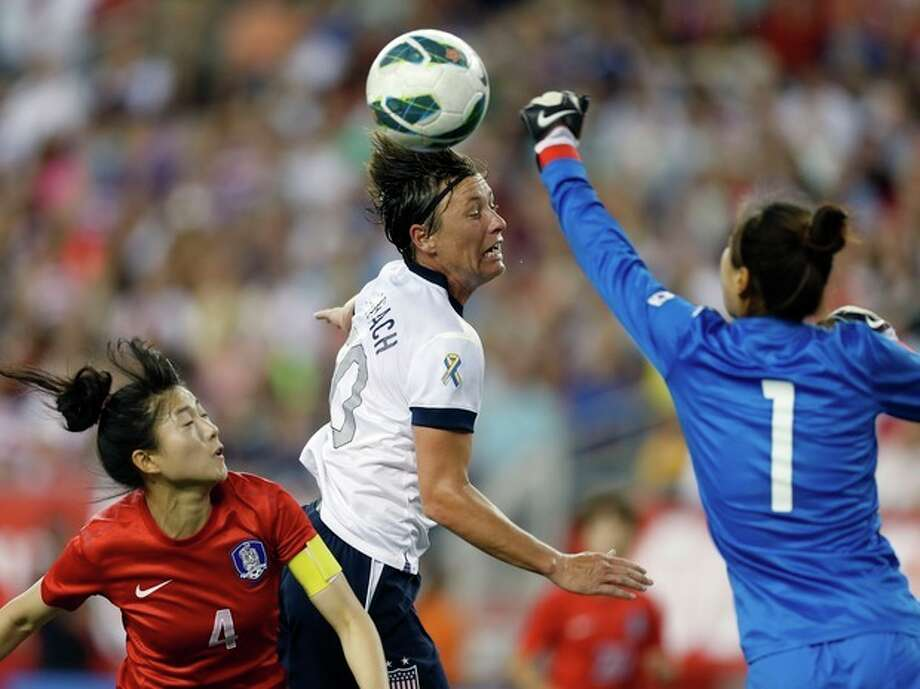 South Korea's Kim Jungmi (1) punches the ball away before United States' Abby Wambach, center, can get a head on it in the second half of an international friendly soccer match in Foxborough, Mass., Saturday, June 15, 2013. The US Women's team won 4-1. (AP Photo/Michael Dwyer) / AP