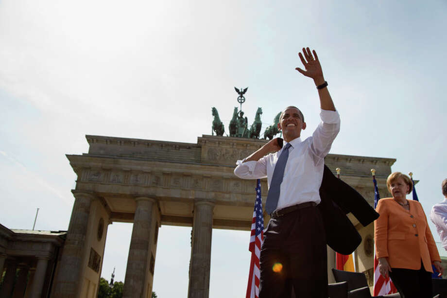 President Barack Obama, accompanied by German Chancellor Angela Merkel, waves to the crowd after speaking at the Brandenburg Gate in Berlin, Wednesday, June 19, 2013. Obama called to reduce the world's nuclear stockpiles, including a proposed one-third reduction in U.S. and Russian arsenals. (AP Photo/Evan Vucci) / AP