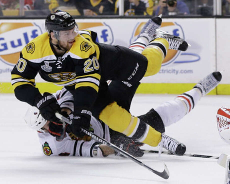 Chicago Blackhawks defenseman Niklas Hjalmarsson, bottom, of Sweden, takes down Boston Bruins left wing Daniel Paille (20) during the second period in Game 3 of the NHL hockey Stanley Cup Finals in Boston, Monday, June 17, 2013. The Bruins scored the game's second goal on the power play that followed. (AP Photo/Elise Amendola) / AP