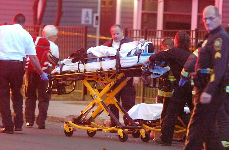 Hour Photo / Alex von Kleydorff. First Responders transport a victim of a drive by shooting on Fort Point Street to an ambulance in Norwalk Tuesday night.