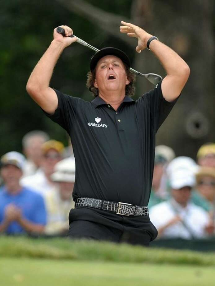 Phil Mickelson reacts as his ball hit from a bunker narrowly misses the hole on an eagle-attempt during the final day of the U.S. Open golf tournament on Sunday, June 16, 2013, at Merion Golf Club in Ardmore, Pa. (AP Photo/The Express-Times, Matt Smith)
