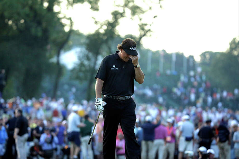 Phil Mickelson reacts after missing a shot on the 18th hole during the fourth round of the U.S. Open golf tournament at Merion Golf Club, Sunday, June 16, 2013, in Ardmore, Pa. (AP Photo/Morry Gash) / AP