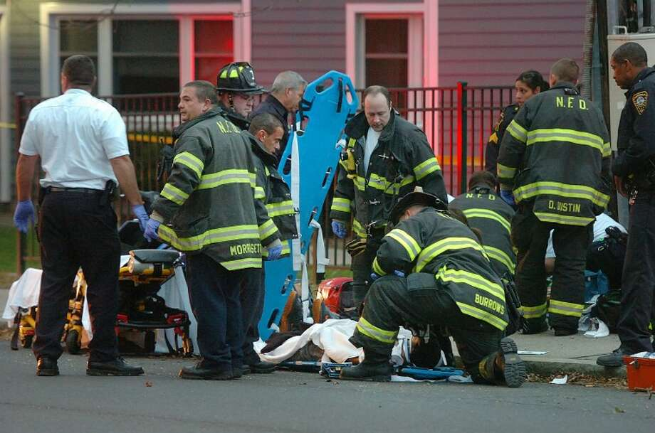 Hour Photo / Alex von Kleydorff. First Responders give medical attention to one of two victims of a drive-by shooting on Fort Point Street in Norwalk Tuesday night.