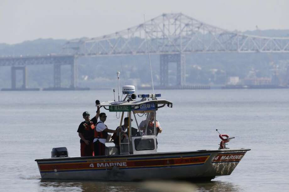 Rescue workers on a boat search the Hudson River south of the Tappan Zee Bridge for two people who are believed to have fallen into the water during a boat crash in Piermont, N.Y. on Saturday, July 27, 2013. Two people are missing and four others are injured after their boat struck a barge under the bridge, according to the Coast Guard. (AP Photo/Julio Cortez)