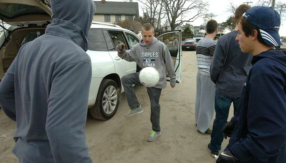 Hour Photo Alex von Kleydorff; Joe Greenwald finds a moment to kick a soccer ball around as the Staples soccer team helps to clean up a teammate's house in Westport.