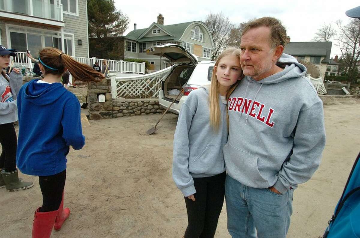 Hour Photo Alex von Kleydorff; Jim Hood and daughter Brittany have all the help they need from the Staples soccer team as clean up at their home on Soundview drive after Hurricane Sandy.