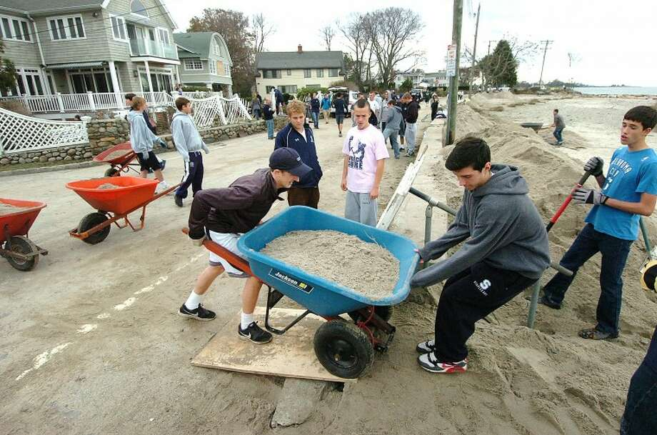 Hour Photo Alex von Kleydorff; Wheelbarrows keep moving as the Staples soccer team helps clear sand and debris from the Hood's house on Soundview Drive in Werstport