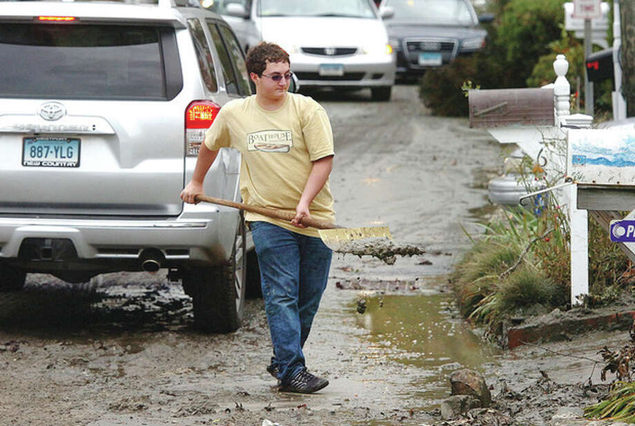 Hour photo / Alex von KleydorffAbove, Sebo Hood moves a wheelbarrow full of beach sand from the front lawn of his familys house on Soundview Drive in Westport. Below, Congressman Jim Himes tours the coastline of Westport / 2012 The Hour Newspapers