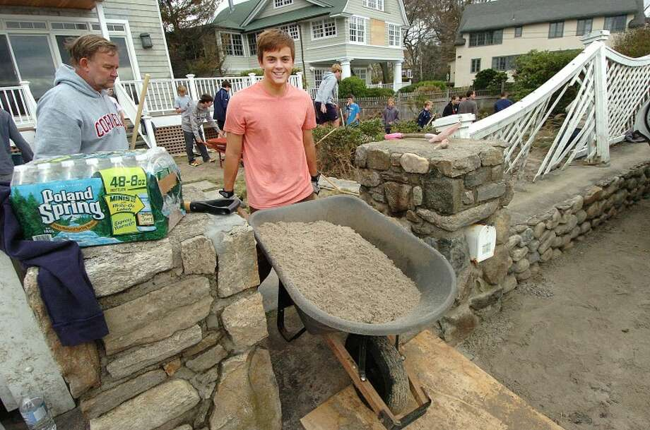 Hour Photo Alex von Kleydorff; Sebo Hood moves a wheelbarrow full of beach sand from the front lawn of his family's house on Soundview Drive in Westport.